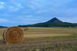 Beautiful golden bales of hay, standing in a big, unspoiled, agricultural field. In the back landscape with a vulcanic hill near the Balaton lake, Hungary. Panoramic, melancholic summer view
