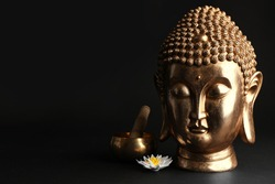Beautiful golden Buddha sculpture with singing bowl and flower on black background. Space for text