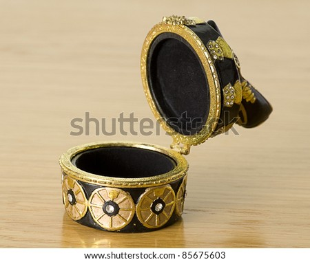 beautiful golden jewelery box isolated on a wooden background