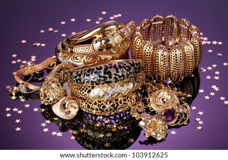 Beautiful golden jewelry on purple background