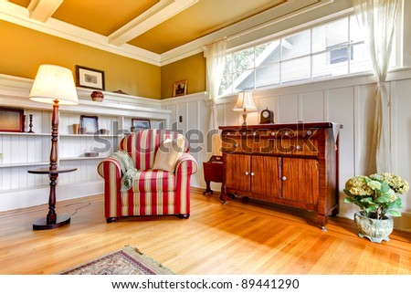 Beautiful golden living room with red chair and white shelves. - stock photo