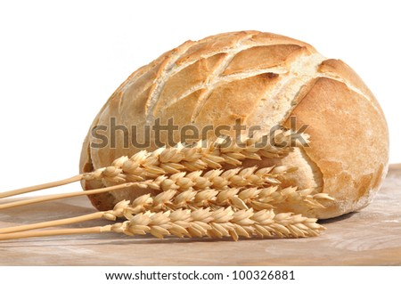beautiful golden loaf of bread and wheat ears on white background
