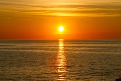 Beautiful golden orange sunset over the ocean. The sun sets turning the sky yellow, orange & red tones & reflects in the ocean.