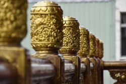 Beautiful golden religious asian art ornament on column pillar at old oriental wooden hand rail in taiwanese spiritual ancient Mazu Wugu Xiandi Temple in traditional Miaoli City, Zhunan, Taiwan, Asia.