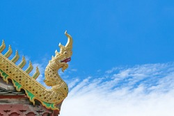 Beautiful golden serpent or naga on art roof of buddhist temple, Gable of the Thai Northern art style, Buddhist temple with blue sky in Temple of Thailand
