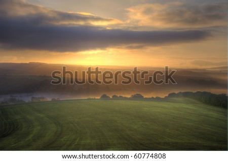 Beautiful golden sunrise over luscious green landscape with glowing sunbeams