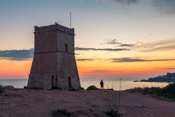 Beautiful golden sunset at Ghajn Tuffieha Tower, above Golden Bay, ancient watchtower built by the Knights of St. John, Golden Bay, Malta
