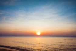 Beautiful golden sunset with blue sky over the horizon on the beach, Thailand. Tropical colorful sunrise from the sea.