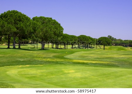 Beautiful golf course against a clear blue sky - stock photo