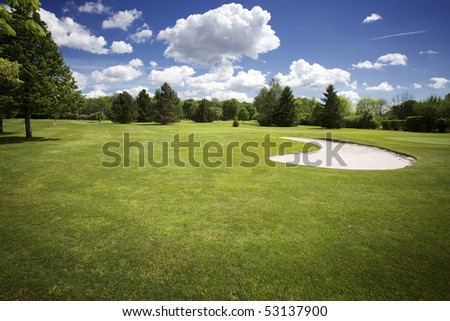 Beautiful golf course with bunker in front of green and cloudy sky.