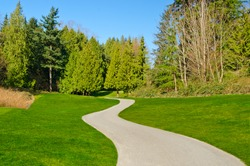 Beautiful golf course with gorgeous green and cart path.