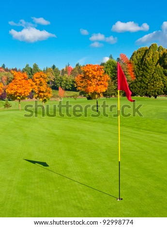 Beautiful golf course with sand bunkers and flag.
