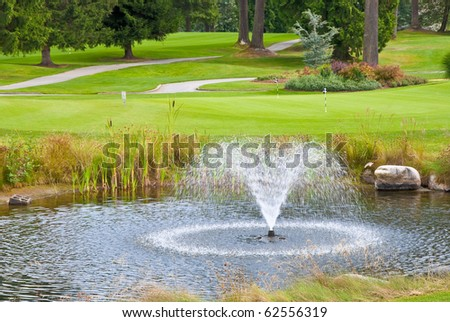 Beautiful golf place with gorgeous green, pond and fountain.