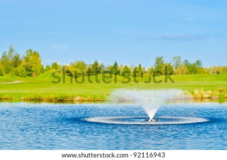 Beautiful golf place with gorgeous green, pond and fountain