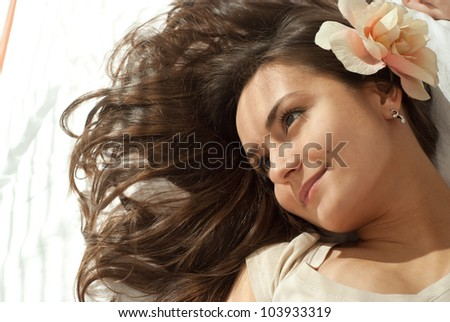 Beautiful good female lying on a pillow on a light background