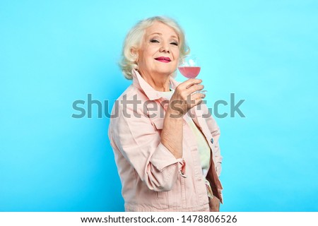 beautiful good looking woman in trendy clothes enjoying drink. close up portrait,isolated blue background.lifestyle,spare time, free time
