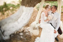 beautiful  gorgeous blonde bride  and stylish groom on the decorated swing on the tree, wedding ceremony  on cyprus