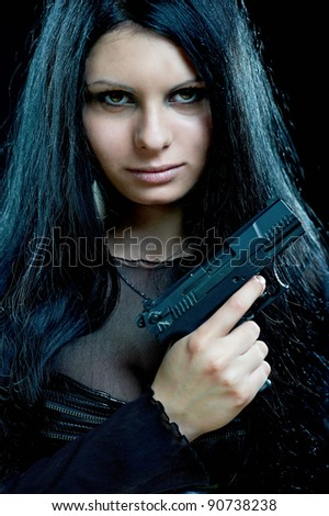 beautiful goth girl with gun on black