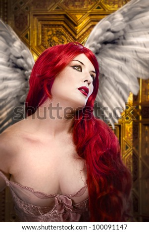 Beautiful gothic sexy angel with wings, red hair over gold background