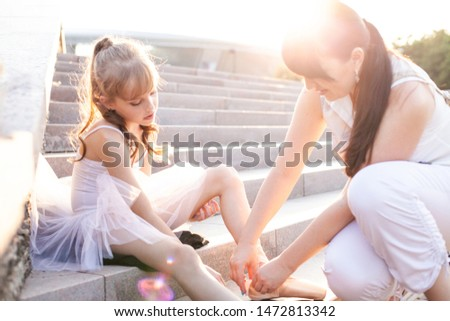 Beautiful graceful little girl ballerina in a white dress and pointe is sitting on the stairs in the park and her mom help to tie pointes shoes