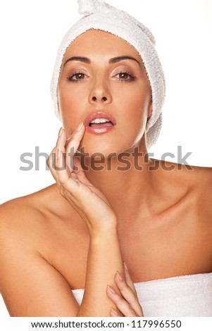 Beautiful graceful woman with her head wrapped in a towel applying lip gloss with the tip of her finger isolated on white