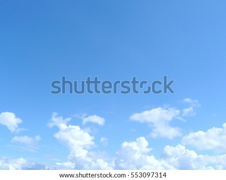 Beautiful gradient of the blue sky with fluffy white cloud in a bright day. #553097314