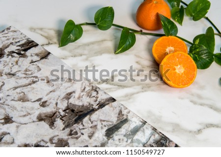 Beautiful grain and texture design of white and brown kitchen granite countertop slab with fresh oranges on white carrara marble. Counter can be used as bathroom vanity top too