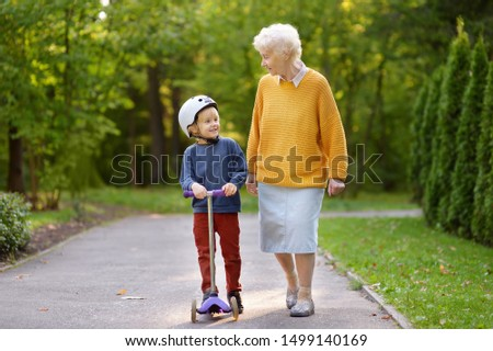 Beautiful granny and her little grandchild walking together in autumn park. Boy riding by scooter. Active family leisure. #1499140169