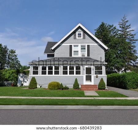 Beautiful gray suburban home gable style house blue sky clouds USA #680439283