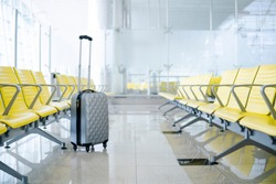Beautiful gray suitcase for hand luggage   in airport terminal with unfocused background of yellow seats, empty waiting area. Vacation trip concept