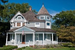 Beautiful gray traditional victorian house.  American Flag hanging over the porch and shows a garden with flowers and trees.  Set against a cloudless blue sky