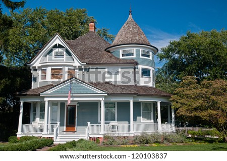 Beautiful gray traditional victorian house.  House has an American Flag hanging over the porch and shows a beautiful garden with flowers and trees.  Set against a cloudless blue sky