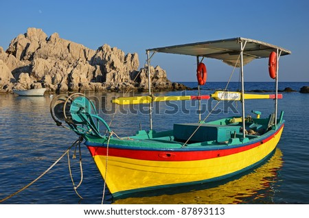 Beautiful greek fishing boat at sunset time, Rhodes island