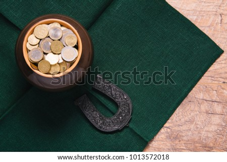 Beautiful green and wooden background for Saint Patric's day celebration. Leprechaun pot of gold. Great party at the 17th March. Patrick's postcard design. Horseshoe as a symbol of the holiday.