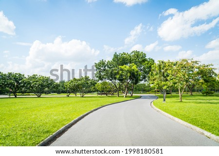 Beautiful green city park with blue sky. Pathway and beautiful trees track for running or walking and cycling relax in the park on green grass field on the side. Sunlight and flare background concept. Stock foto ©