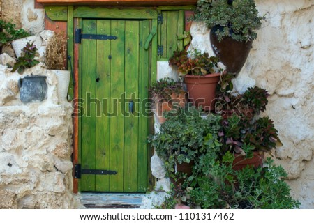 Beautiful green door and flower pots on old stone wall in old city Acre, Israel.  Stone wall with a fairytale green door and flowers in pots. Green background with a door and flower pots in old Acre.