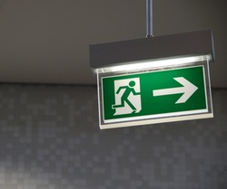 beautiful green emergency exit sign hanging on a ceiling
