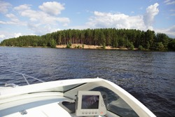 Beautiful green forestry riverbank with sandy beach on Volga river, view from motor boat cockpit with chartplotter device on blue sky with white clouds background, summer day scenery river landscape