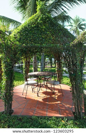 Beautiful green gazebo pavilion in the resort garden