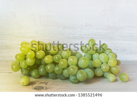 Beautiful green grapeshot with sunny highlights on the grey wooden background. #1385521496