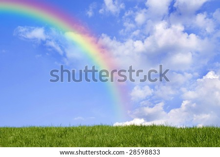 Beautiful green grass against blue sky and rainbow.