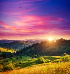 Beautiful green hills glowing by warm sunlight at twilight. Dramatic scene. Colorful sky, red clouds. Carpathian, Ukraine, Europe. Beauty world.