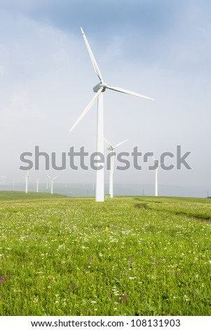 Beautiful green meadow with Wind turbines generating electricity
