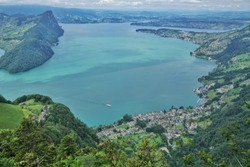Beautiful green meadows and mountains overlook the turquoise waters of Switzerland's lake Lucerne, Vitznau town nestles on the bank.