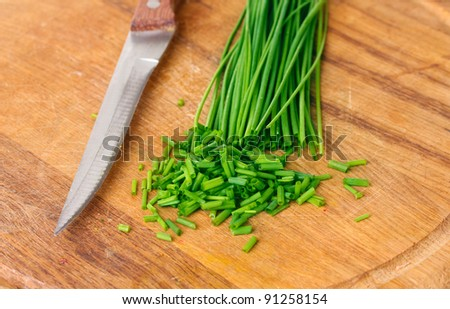 beautiful green onion chives and knife on wooden board closeup