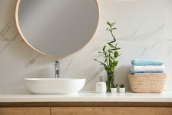 Beautiful green plants near vessel sink on countertop in bathroom. Interior design elements