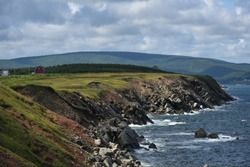 Beautiful green plateau above the sea and waves on the rocky shore in Nova Scotia on the Cabot Trail on Cape Breton Island.