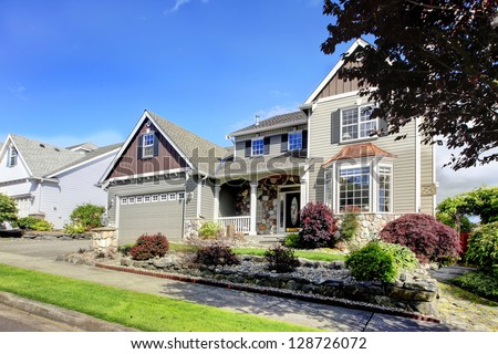 Beautiful grey new classic American home exterior with natural stone.