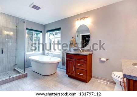 Beautiful grey new modern bathroom interior with two separate sinks, tub and glass shower.