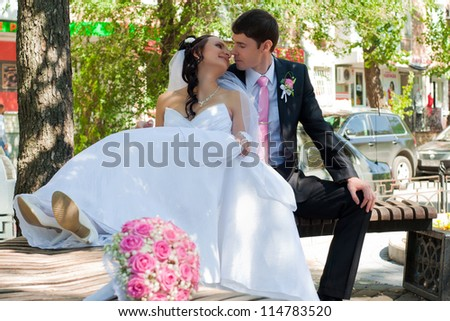 beautiful groom and the bride sit on a bench in park among green foliage